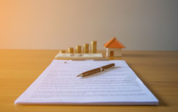Small house and coins beind documents