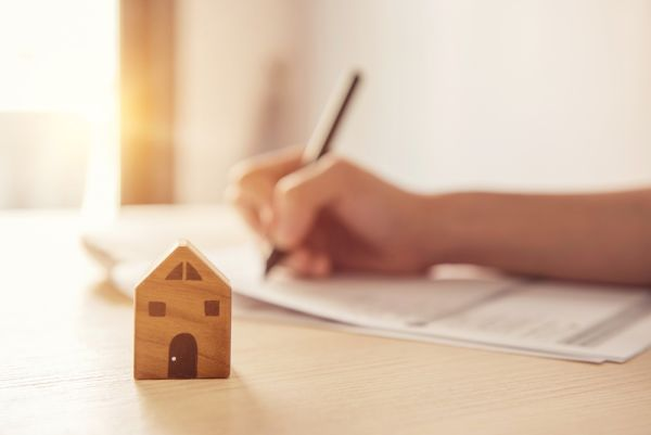Small Wooden home in front of a document being filled out