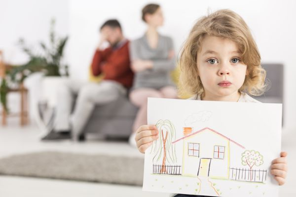 Little girl holding her drawing of a home