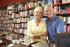 Business owning couple standing happily in their bookstore