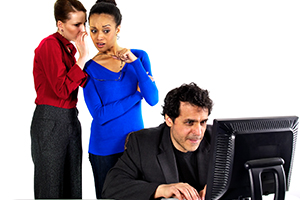 Women gossiping behind a man using the computer