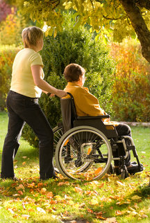 Woman pushing another woman in a wheelchair in the woods