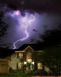 Lightning striking behind a home during a storm
