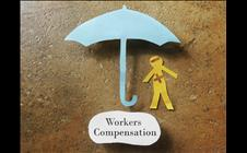 "Paper man under a paper umbrella labeled ""Workers Compensation"""