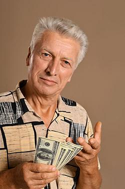 Elderly man holding several hundred dollar bills
