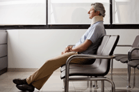 Man in a neckbrace sitting in a waiting room