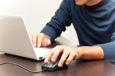 Guy using a laptop with a mouse attachment