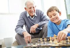 Grandpa watching his son play chess