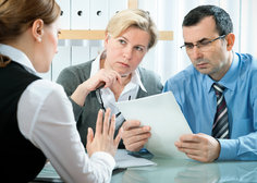 Couple looking inquisitviley at a lawyer while holding paper