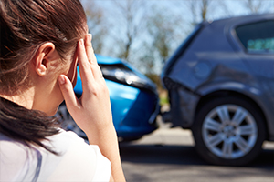 Stressed woman holding her head, looking at a fender bender