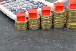 Stacks of coins with toy houses on top