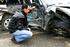 Man in a leather jacket crouched down look at his totalled car