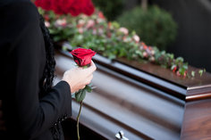 Woman holding a rose over a coffin