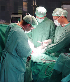 Three doctors performing surgery