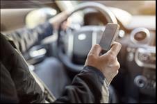 Man looking at phone while driving