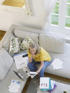 Woman looking over bills on her couch