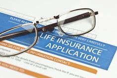 Life Insurance Application with glasses on top
