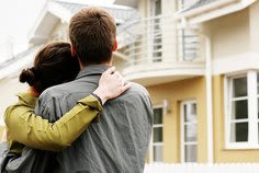Couple hugging in front of new house