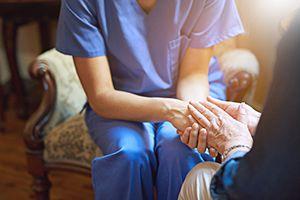 Caregiver holding the hand of a senior