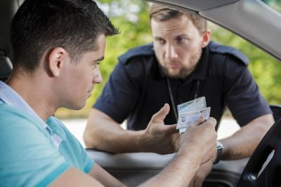 Man giving his license and registration to the police officer