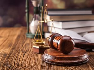 gavel, scales of justice, hourglass, and books on wood table