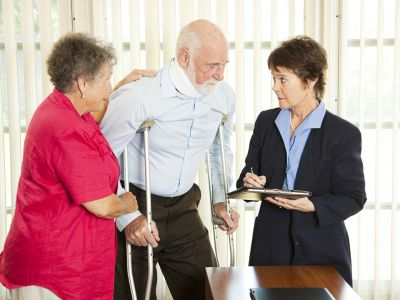 Elderly couple, man on crutches, talking to a woman in a suit