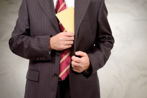 man putting envelope in his suit jacket