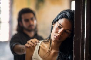 sad woman leaning against doorway with man touching her shoulder