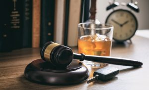 gavel, breathalyzer, and an alcoholic drink on table