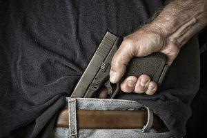 man tucking firearm into belt
