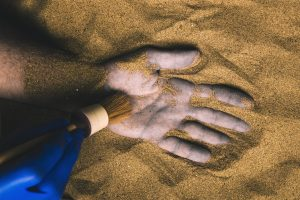 brushing sand off a discolored hand