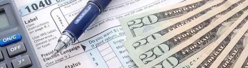 A calculator, a pen, twenty dollar bills, and a 1040 tax form