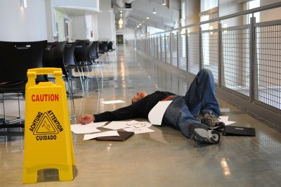 man lying on the ground with papers scattered in front of a caution wet floor sign