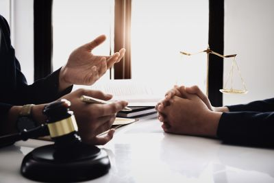 two people meeting with gavel and scales of justice on table