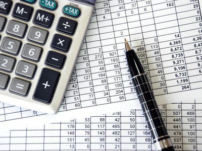 calculator, pen, and spreasheets