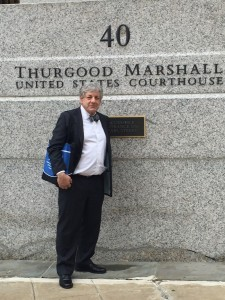 Man in suit holding bag in front of Thurgood Marshall United States Courthouse building