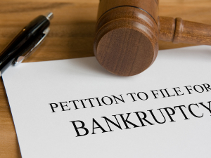 "Gavel, pen, and paper that reads ""Petition to file for bankruptcy"""