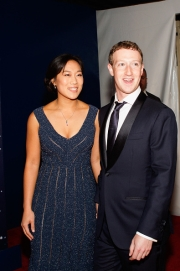 Priscilla Chan pictured in a long navy dress and Mark Zuckerberg in a suit smiling for a photo at the Breakthrough Prize Awards Ceremony