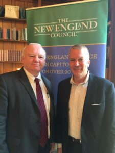 Attorney Foley and U.S. Senator Daniel Sullivan standing and smiling in front of a sign that says The New England Council