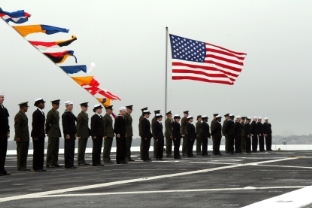 Men and women in uniform standing at attention in front of an American flag