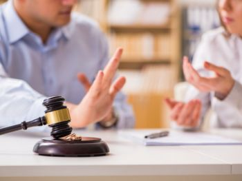 Man and woman arguing while documents and a gavel sit on the table