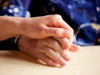 Close up of a young hand holding an older hand