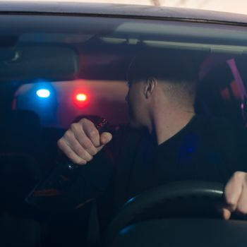 Driver with a beer bottle in hand being pulled over