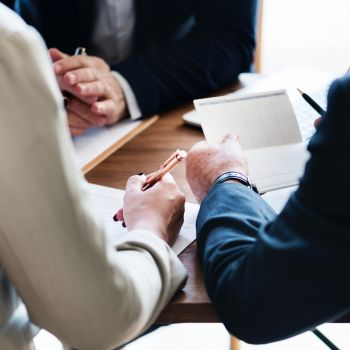Three people at a table. One is holding a pen, one is holding paper, and one has their hands clasped.