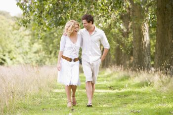 Couple walking on a grassy path together while smimling