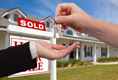 Hand dropping keys into another hand in front of sold sign outside a house