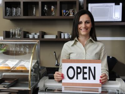 Woman standing behind counter holding an open sign
