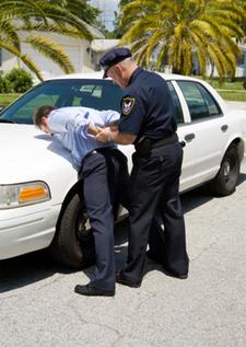Cop arresting a man on the hood of a car