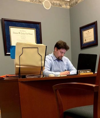 Attorney Ryan A. Slep sitting and writing at his desk
