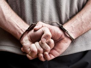 Close up of man's hands behind his back in handcuffs